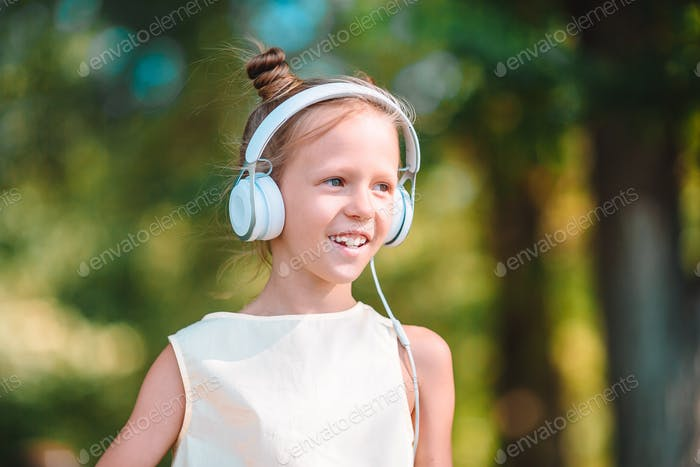 Little adorable girl listening music in the park