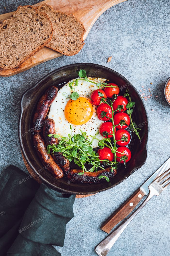 Breakfast time, fried egg with sausages and cherry tomatoes in a black iron pan, served microgreens