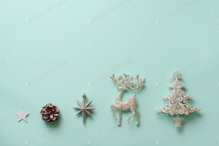 Festive silver dear, stars, fir-tree, cone on blue background with copy space. Christmas and new