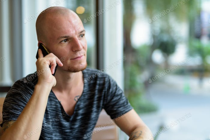 Young handsome bald man thinking while talking on mobile phone i