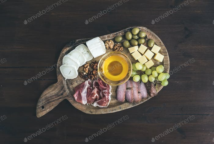 Wine appetizers set: meat and cheese selection, honey, grapes, w
