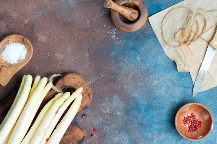 Raw organic white asparagus spears on a wooden board as a healthy diet food on a dark stone