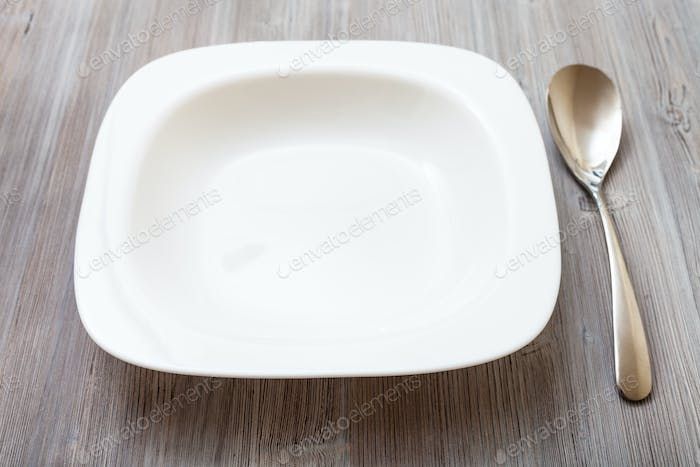 white square bowl and spoon on gray brown table