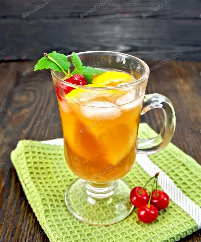 Lemonade cherry and orange in wineglass on dark board