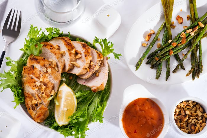 Gegrillte Hähnchenbrust mit gegrilltem Spargel und Zitronenscheibe. Paleo-Diät. Gesunde Ernährung
