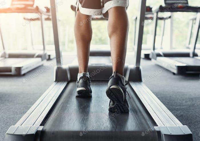 Мужские ноги на беговой дорожке в фитнес-клубе, здоровый образ жизни