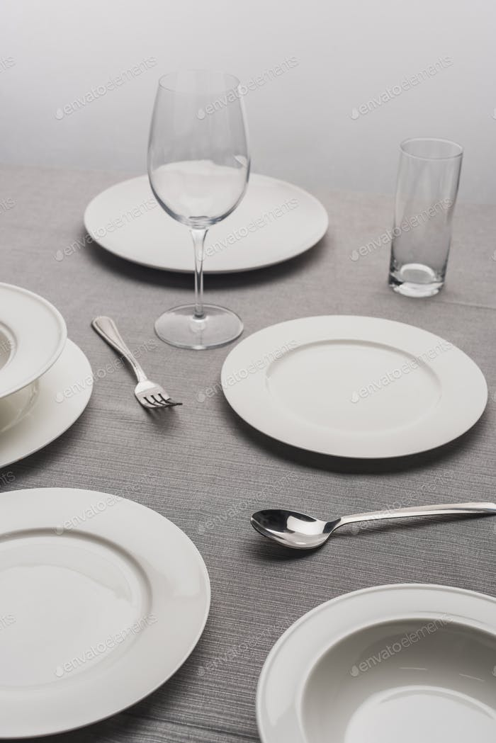 Serving Dinnerware With Empty Glasses on Grey Surface