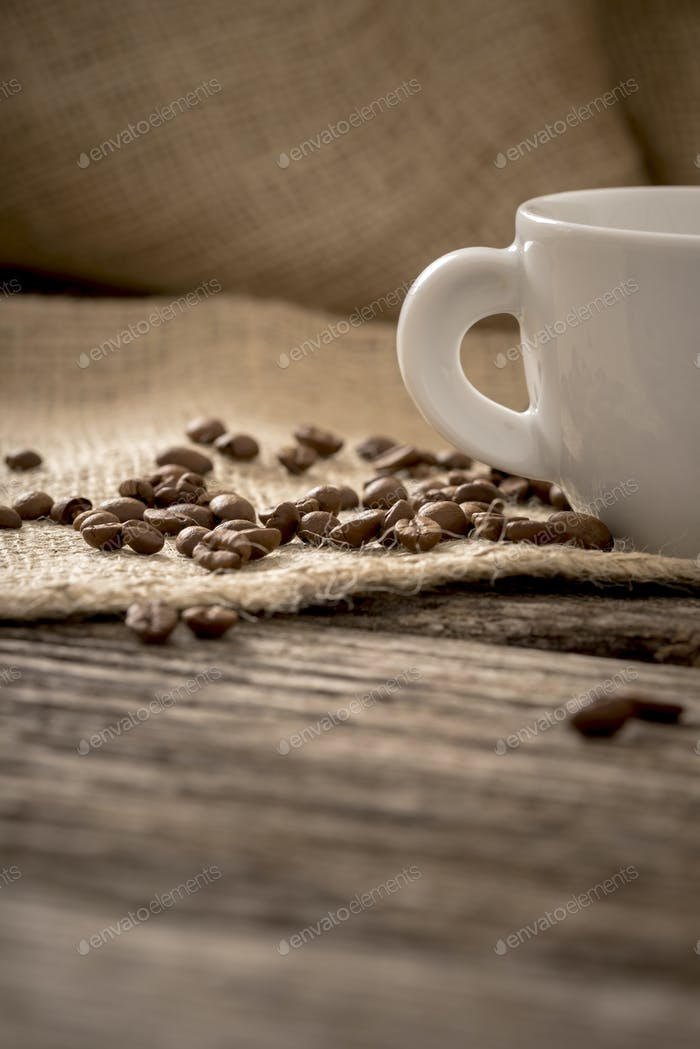 Low angle view of coffee beans scattered on linen cloth lying on