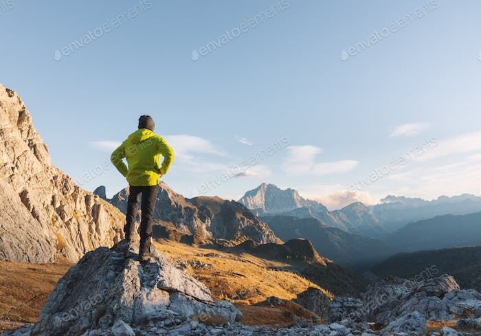 Sporty man standing on the stone against mountains at sunset