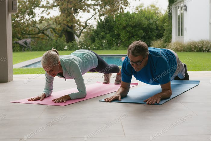 Front view of determined active senior Caucasian couple doing plank exercise in the porch at home
