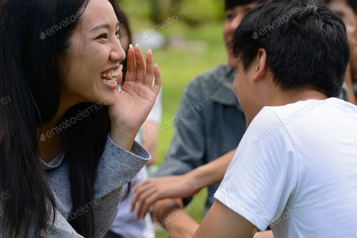 Two young Asian friends whispering together at the park