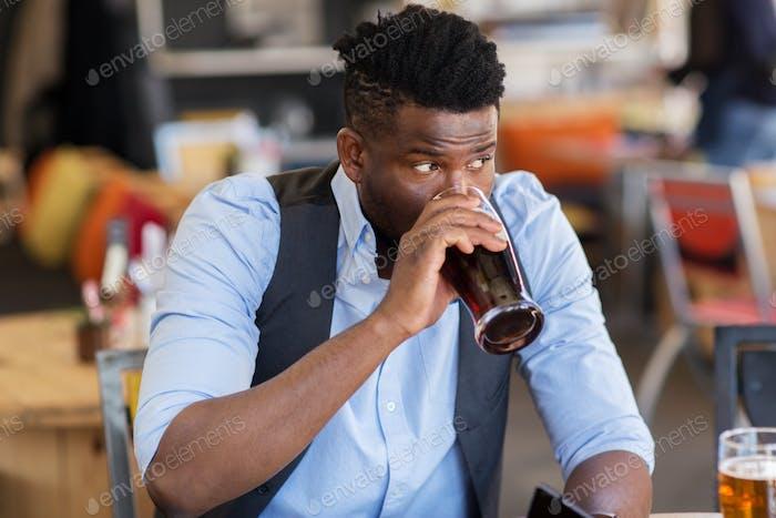 man drinking draught beer at bar or pub