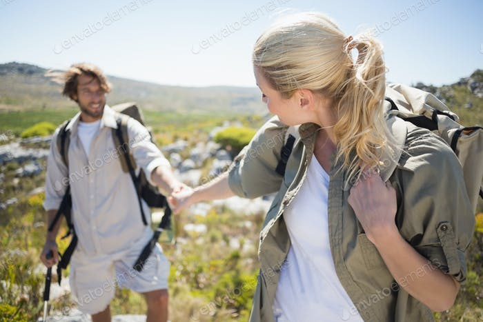Hiking couple walking on mountain terrain on a sunny day