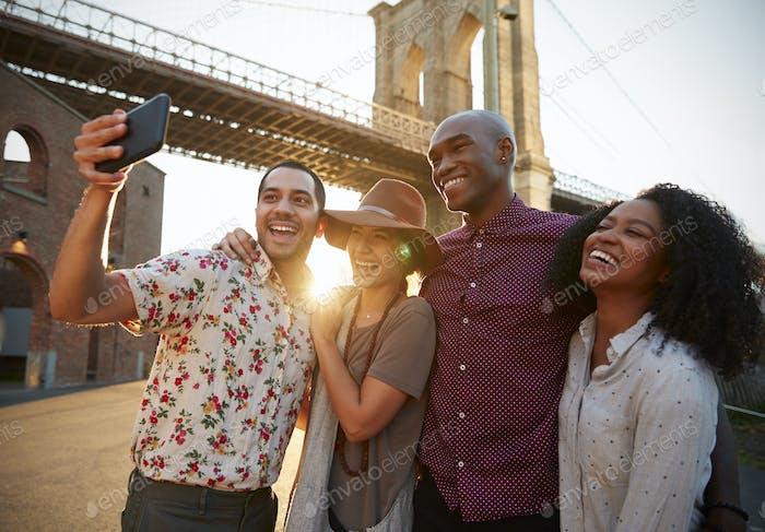 Group Of Friends Posing For Selfie In Front Of Brooklyn Bridge