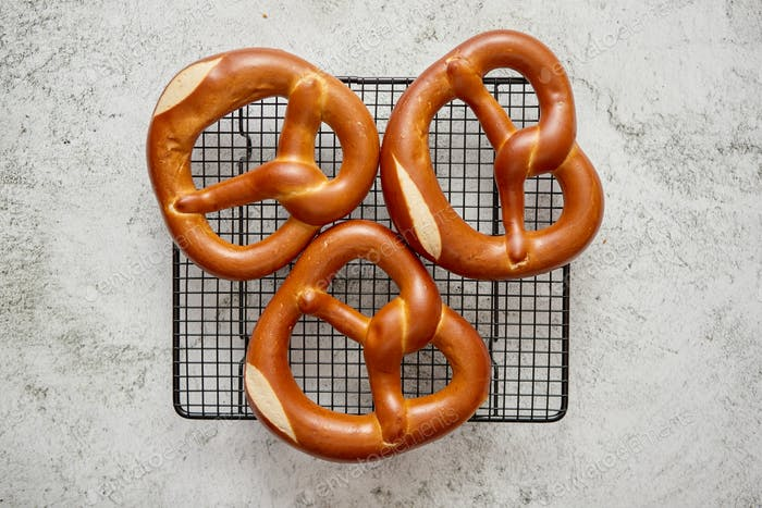 Three german fresh baked pretzel buns placed on steel grill frame