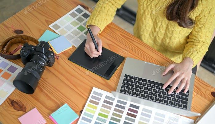 Designer arbeiten an einem Zeichentablett und Laptop.