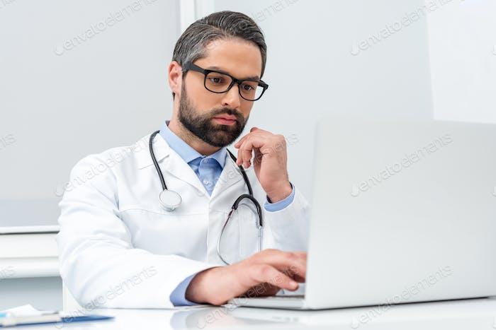 gut aussehender konzentrierter Arzt mit Laptop
