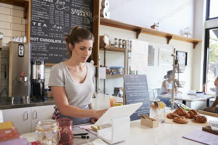 Frau arbeitet an der Kasse in einem Café, Weitwinkel