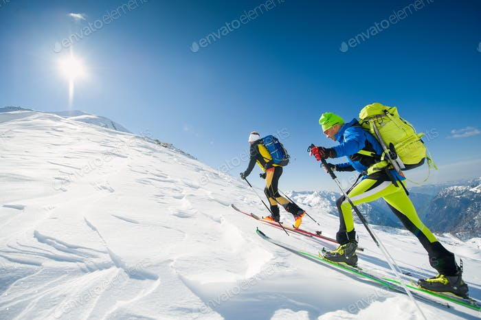 Cross country skiing team couple of men towards the summit