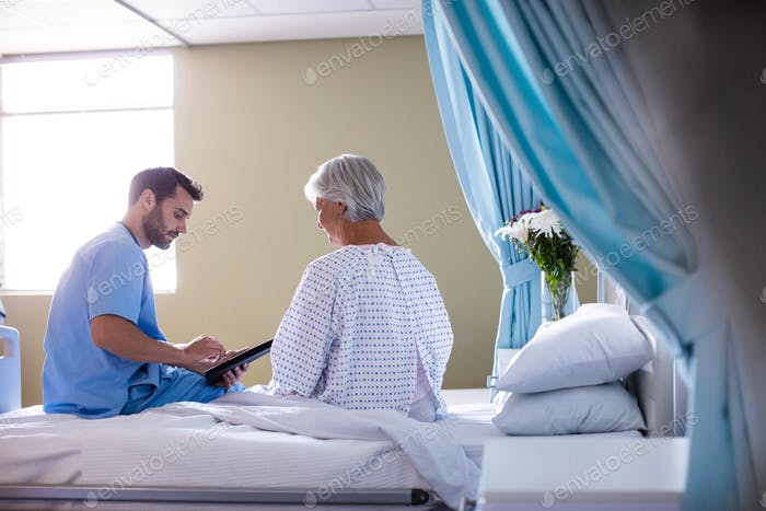 Male doctor showing medical report to female senior patient on a digital tablet