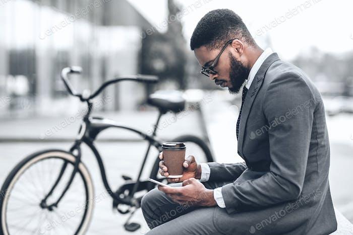 Handsome businessman browsing internet during coffee break