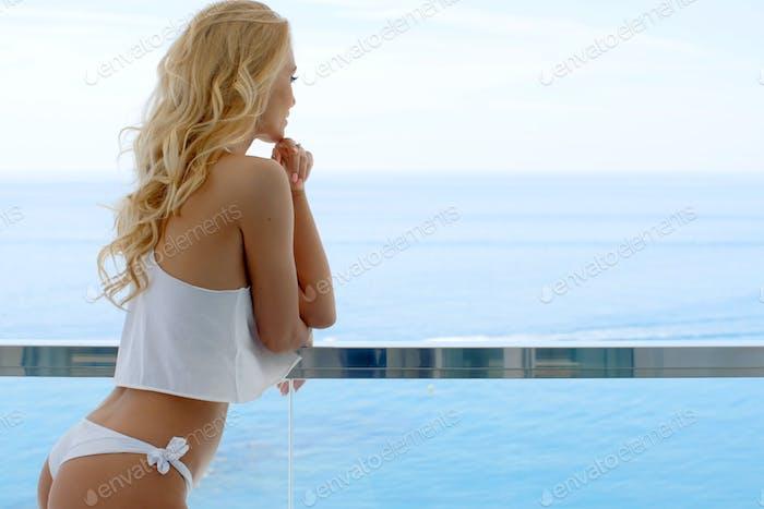 Blond woman wearing white bikini and silky top