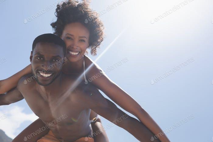 Man carrying beautiful mixed-race woman piggyback at beach on a sunny day