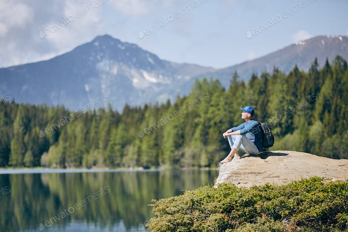Tourist resting on rock above lake