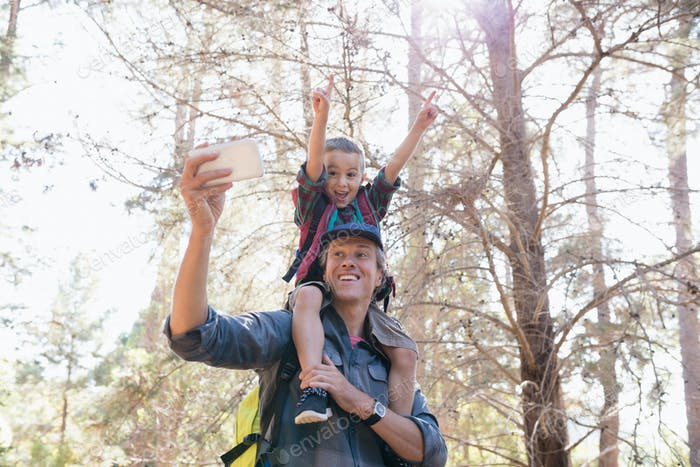 Low angle view of father carrying son on shoulders while taking selfie