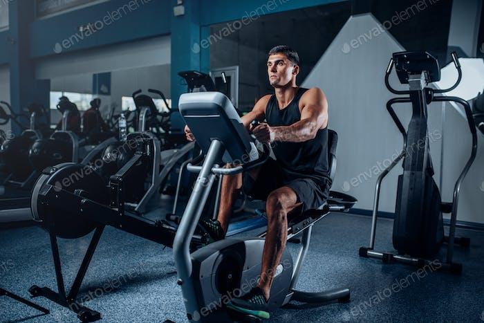 Muscular athlete training legs on exercise machine