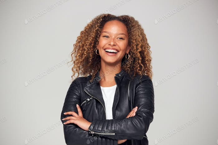 Waist Up Studio Shot Of Happy Young Woman With Folded Arms Wearing Leather Jacket Smiling At Camera