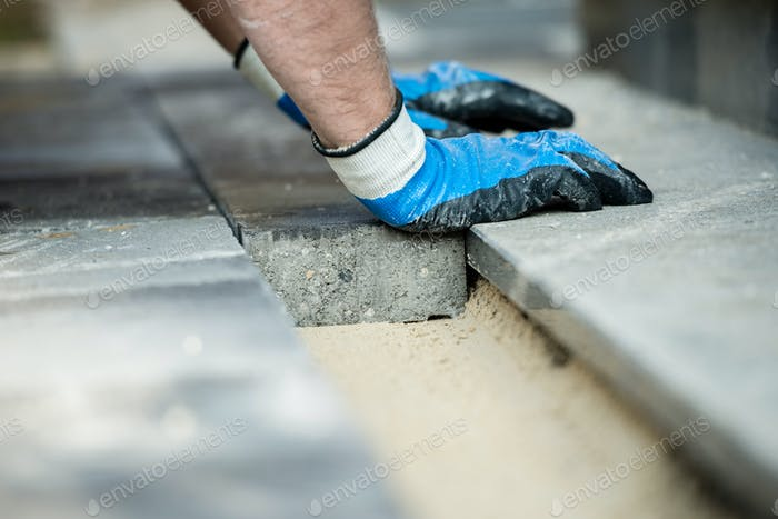 Builder laying new paving bricks