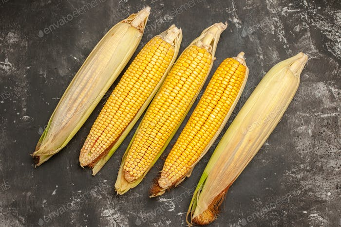 top view fresh yellow corns on dark background raw color photo