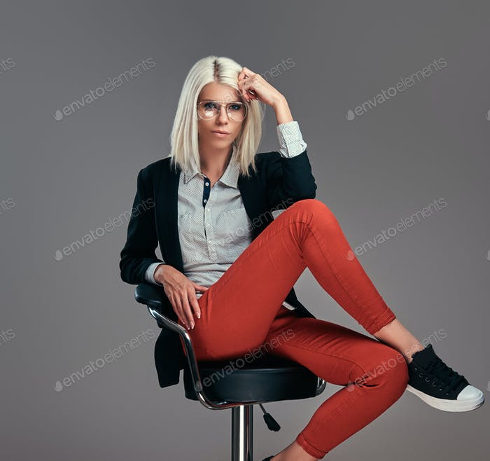 Smart fashionable blogger female in modern clothes and glasses in a studio
