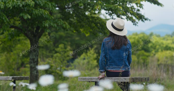Woman look around the landscape and sit on the wooden bench