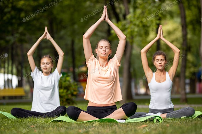 Three young girls doing yoga sitting on yoga mats on green grass in the park on a warm day