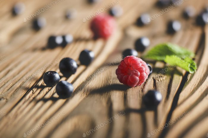 Ripe organic Raspberries and Blueberries on the top of wooden ta