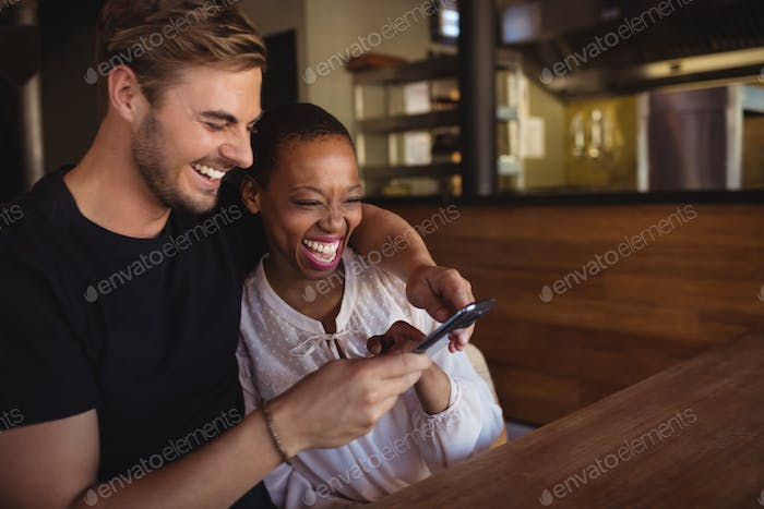 Happy couple using mobile phone