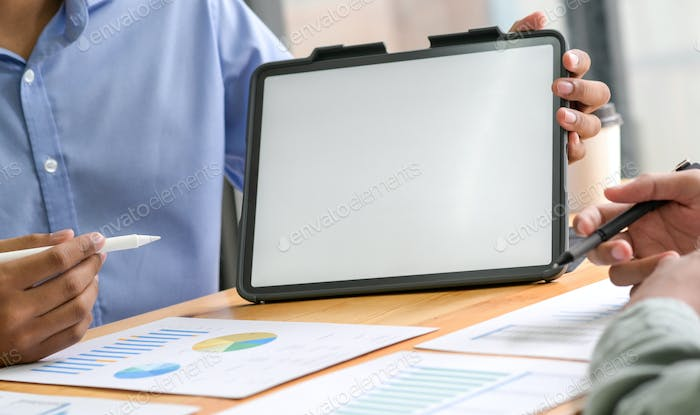 Businesspeople use tablet to analyze earnings data.