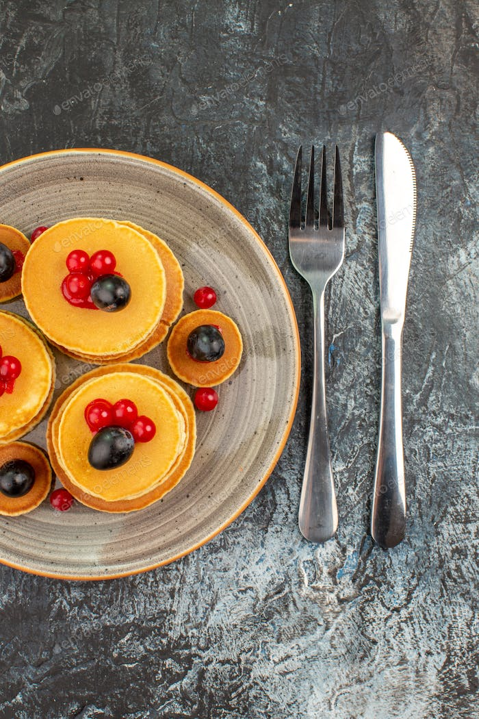 Vertical view of tasty pancakes with fruits