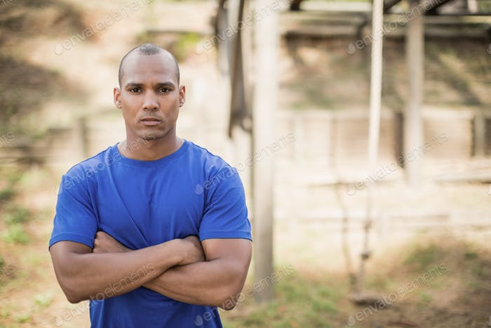Portrait of fit man standing with arms crossed during obstacle course