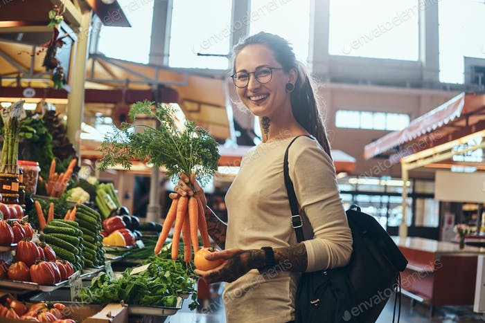 Tattooed young lady is choosing sesonal vegetables at market
