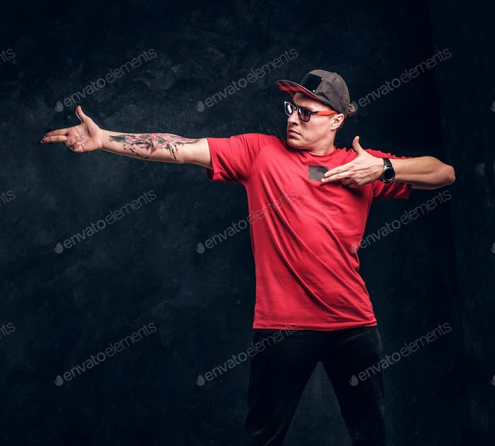 Stylish man with a tattoo on his hand dressed in a hip-hop style, posing for a camera