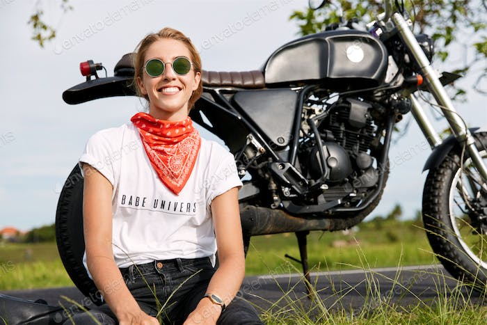 Sporty smiling female biker travels on motorbike being active, wears casual clothing and sunglasses,
