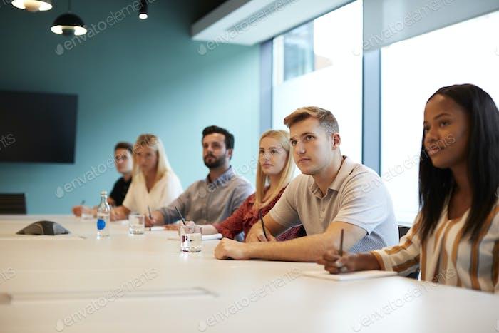 Grupo de jóvenes candidatos sentados en la mesa de la sala de juntas escuchando la Presentación
