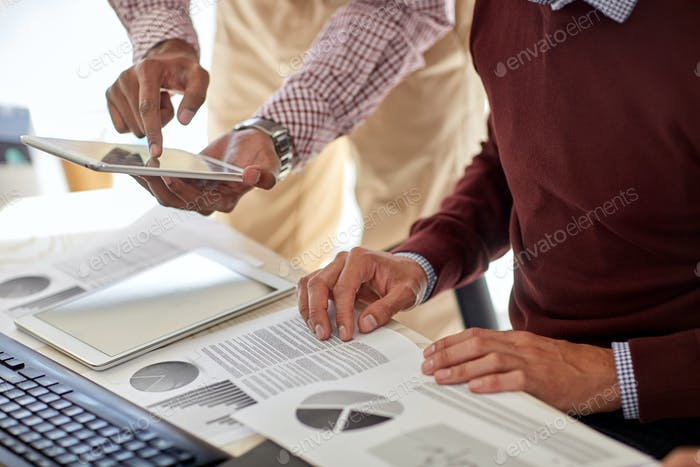 businessmen with tablet pc and charts at office