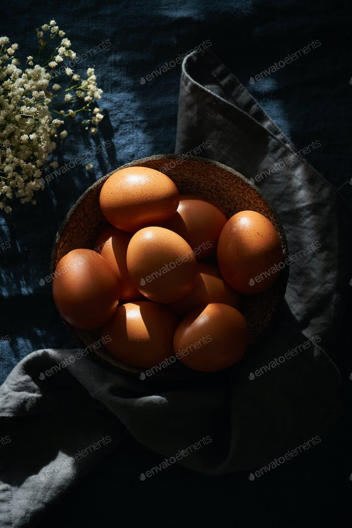 Unusual Easter on dark background. Bowl of brown eggs with hands, vertical