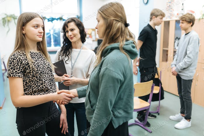 Teacher talks at school with two conflicted teenage girls and convinces them to make it up