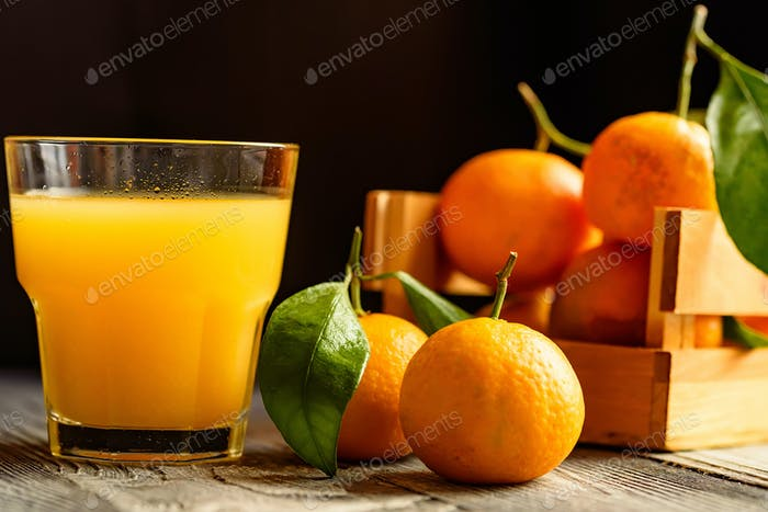 Glass of fresh juice and mandarins on table