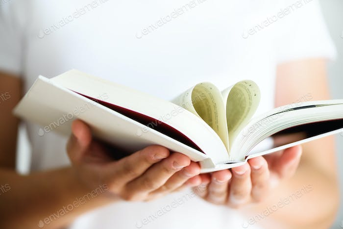 Young girl in white T-shirt reading opened book with shape of heart, love concept. Copy space